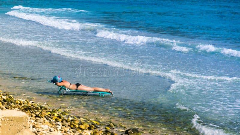 Donna alla spiaggia sulla sedia di salotto, in mezzo all'acqua, alla spiaggia ed all'oceano, con il cappello blu ed il mare con immagine stock libera da diritti