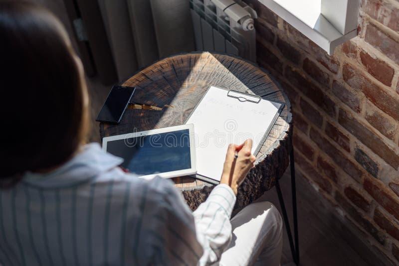 Donna alla tavola davanti alla finestra con una compressa e un taccuino, business plan, indipendente, partenza fotografie stock libere da diritti