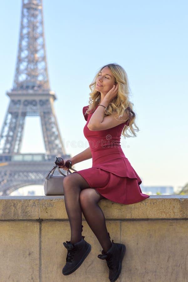 Donna alla torre Eiffel Parigi, Francia Giovane ragazza turistica in un vestito romantico rosso da Borgogna che ammira le viste R immagini stock