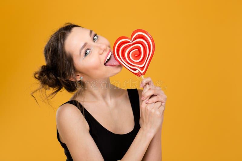 Donna allegra adorabile che lecca la lecca-lecca a forma di dell'innamorato immagini stock
