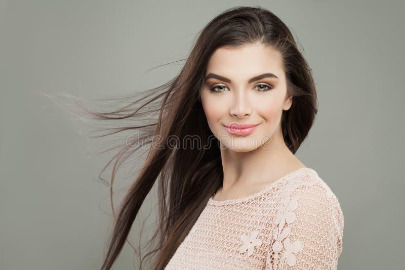 Donna allegra castana con capelli sani scuri lunghi fotografia stock libera da diritti