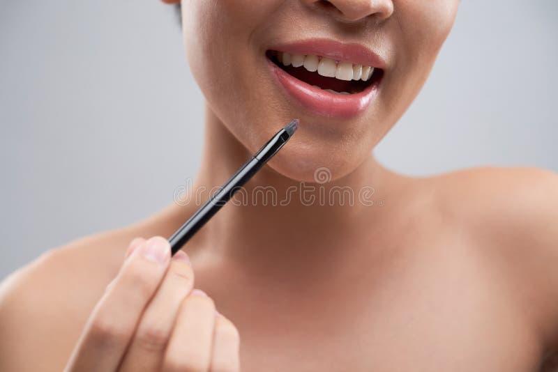 Donna allegra che applica rossetto immagine stock