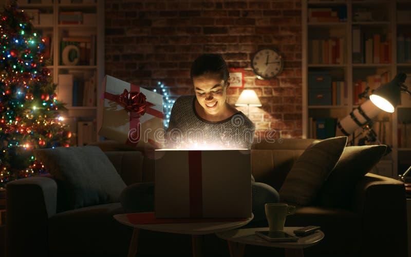 Donna allegra che apre i suoi regali di Natale immagini stock