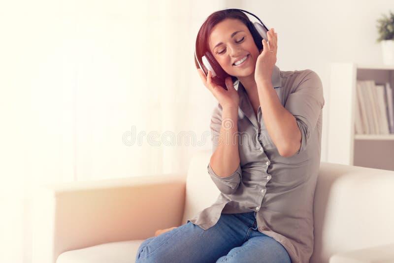Donna allegra che ascolta la musica con le cuffie immagini stock