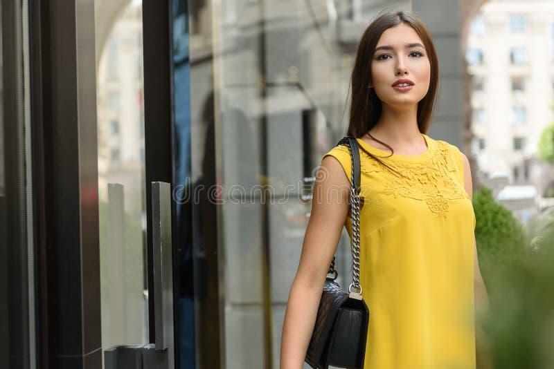 Donna allegra che aspetta qualcuno vicino alla costruzione immagine stock libera da diritti