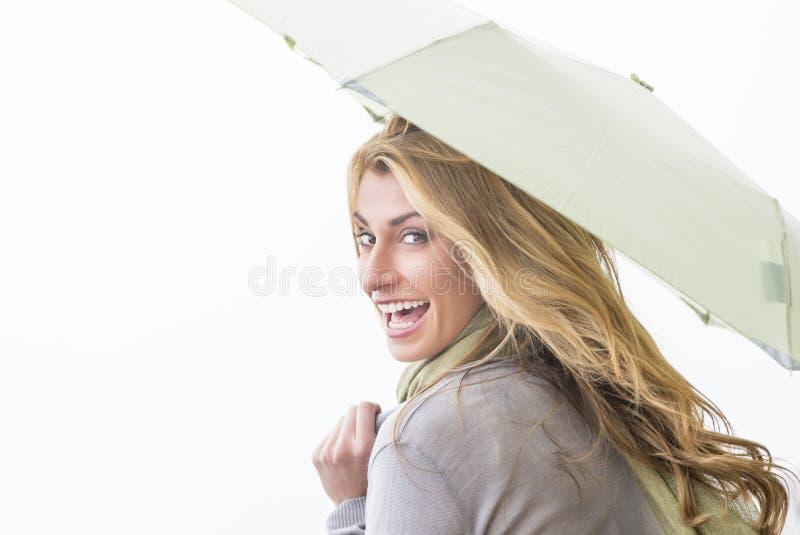 Donna allegra che esamina spalla mentre tenendo ombrello immagine stock