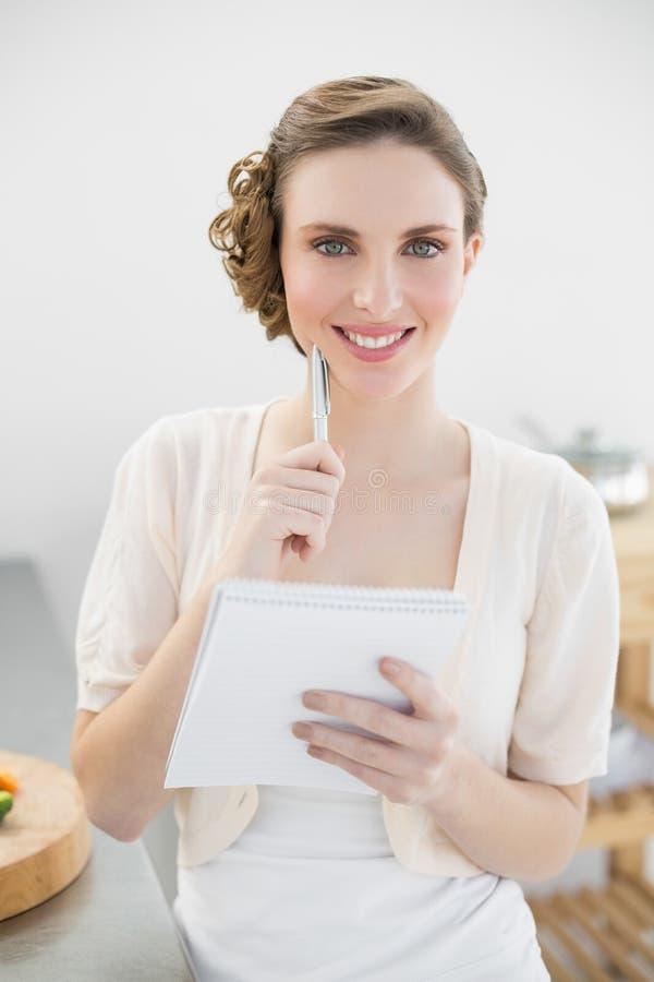 Donna allegra che pensa mentre redigendo la lista di acquisto nella sua cucina immagine stock libera da diritti