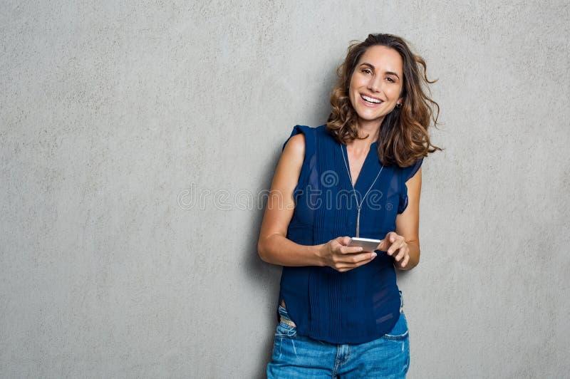 Donna allegra che per mezzo del telefono immagini stock libere da diritti