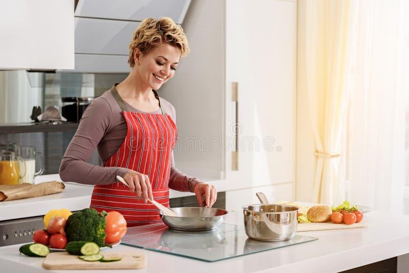 Donna allegra che prepara prima colazione sana fotografia stock libera da diritti