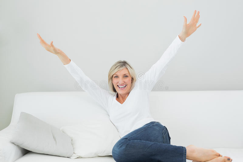 Donna allegra che si siede sul sofà con le armi stese a casa immagini stock