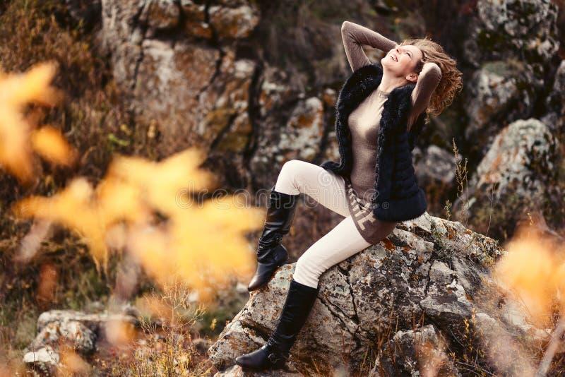 Donna allegra che si siede sulle rocce immagine stock