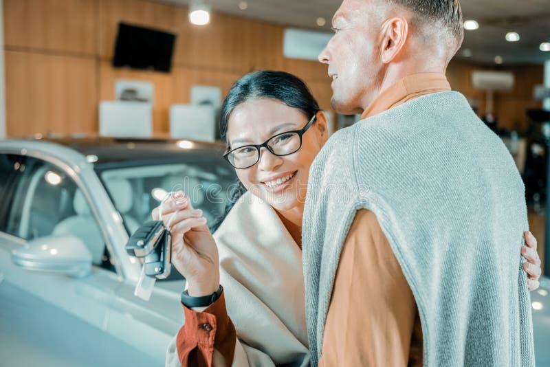 Donna allegra che tiene le chiavi della sua nuova automobile fotografie stock