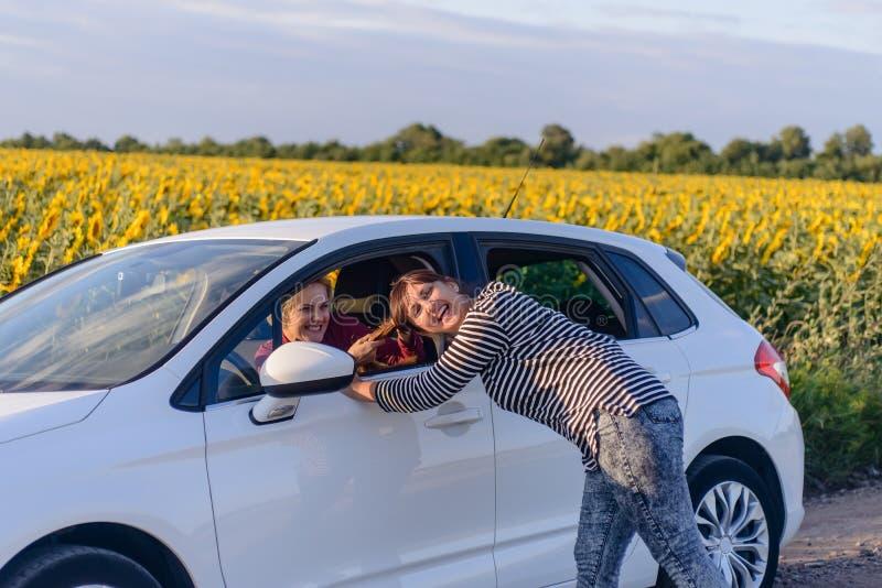 Donna allegra che tira i capelli di un driver femminile fotografia stock
