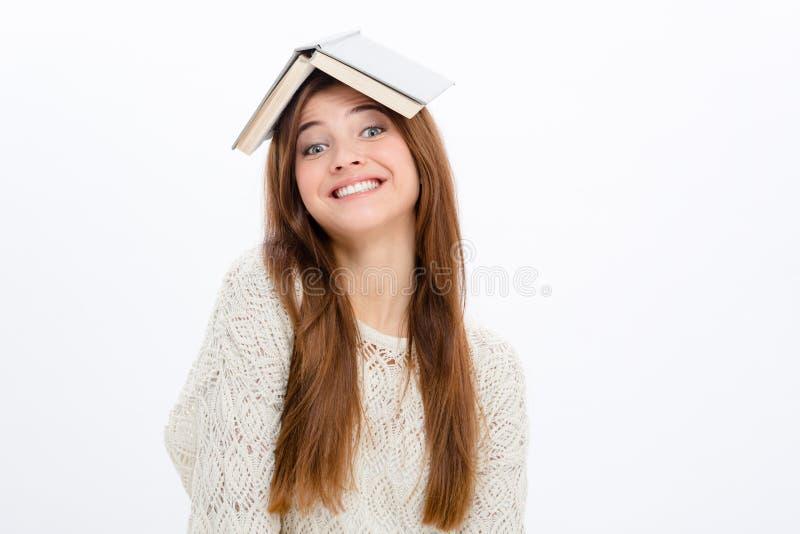Donna allegra comica allegra con il libro aperto sulla sua testa immagini stock