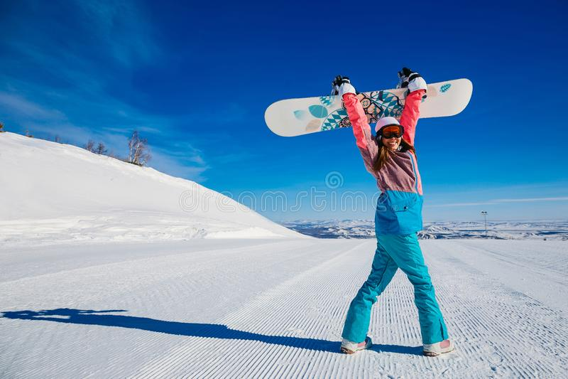 Donna allegra con lo snowboard nelle montagne nell'inverno immagine stock libera da diritti