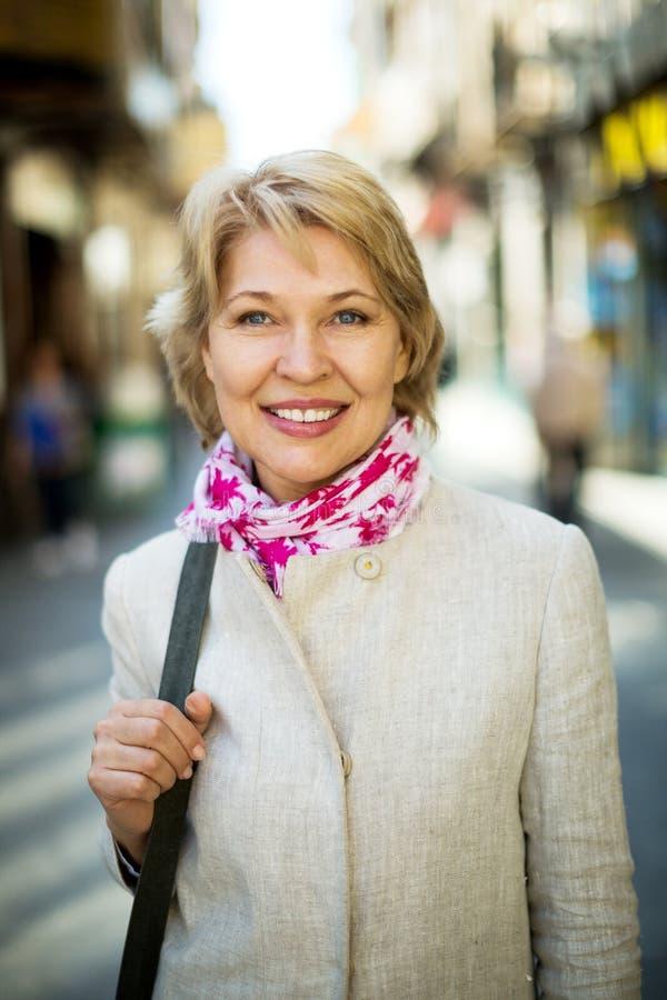 Donna allegra del pensionato che ha una passeggiata in città fotografia stock libera da diritti