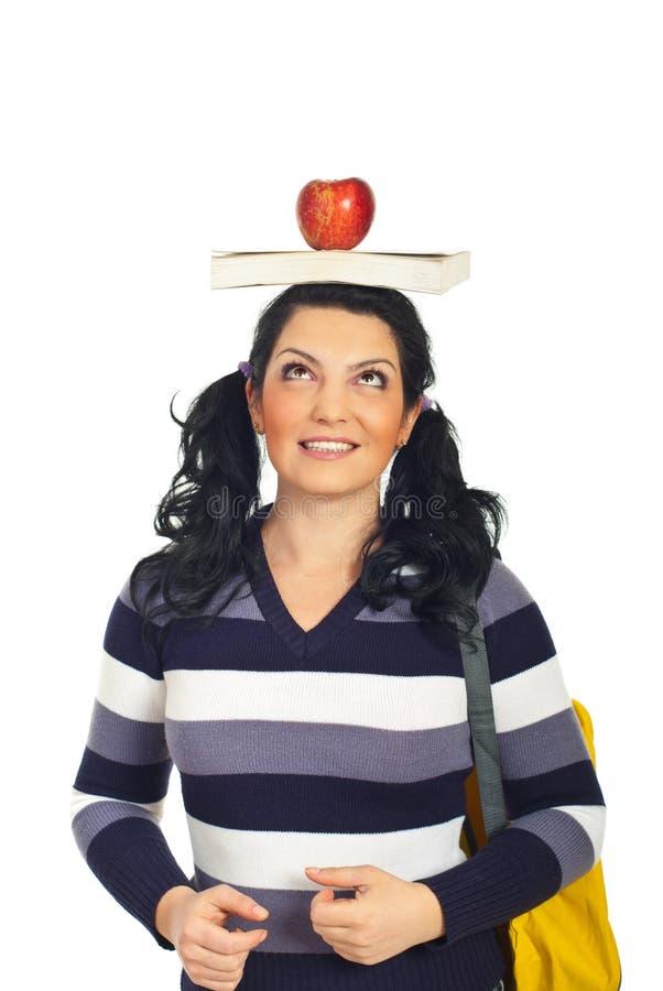 Donna allegra dell'allievo con il libro sulla testa immagini stock libere da diritti