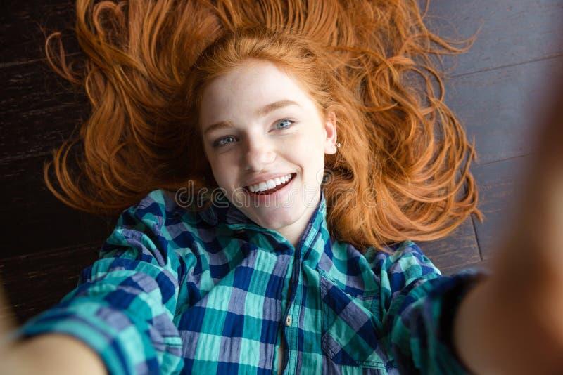 Donna allegra della testarossa che fa immagine di auto che si trova sul pavimento fotografia stock libera da diritti