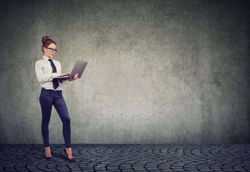 Donna allegra di affari che per mezzo del computer portatile fotografia stock libera da diritti