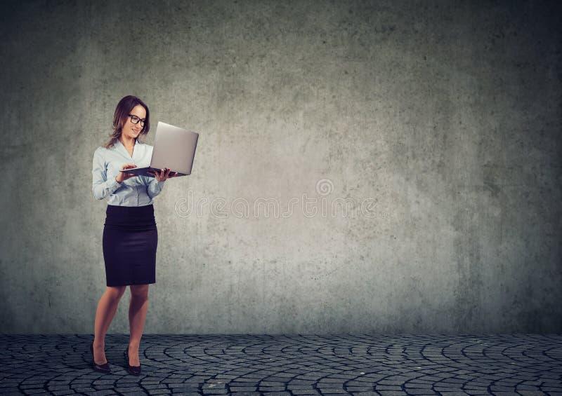 Donna allegra di affari che per mezzo del computer portatile immagine stock