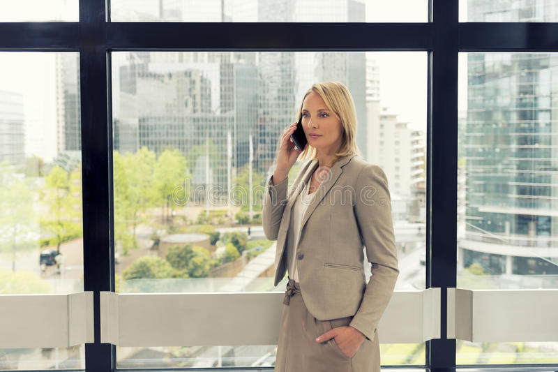 Donna allegra di affari sul telefono cellulare all'ufficio moderno Buildi immagine stock libera da diritti