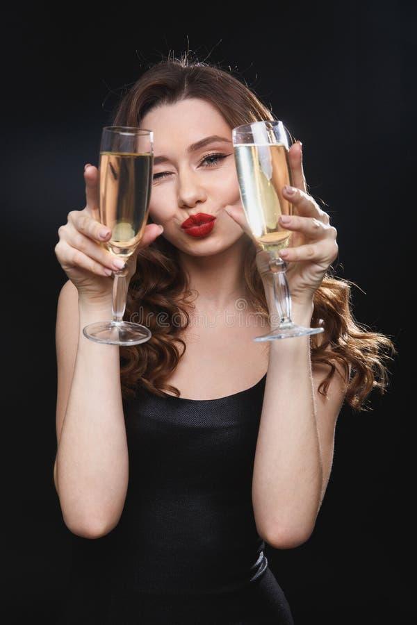 Donna allegra felice che tiene due vetri di champagne e di sbattere le palpebre fotografia stock