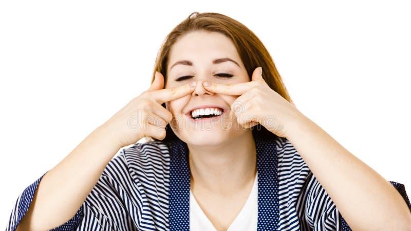 Donna allegra felice che tocca il suo naso fotografia stock