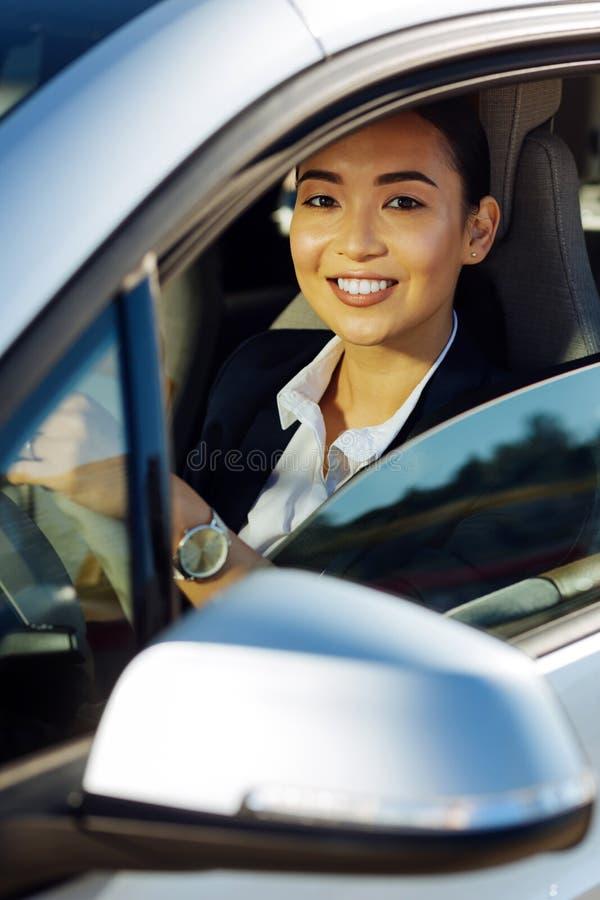 Donna allegra positiva che si siede dietro la ruota fotografia stock