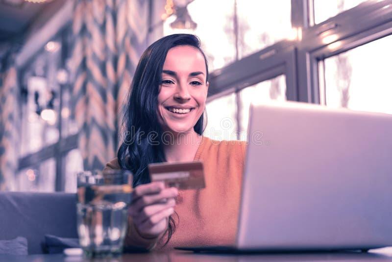 Donna allegra positiva che usando la sua carta contante immagine stock libera da diritti