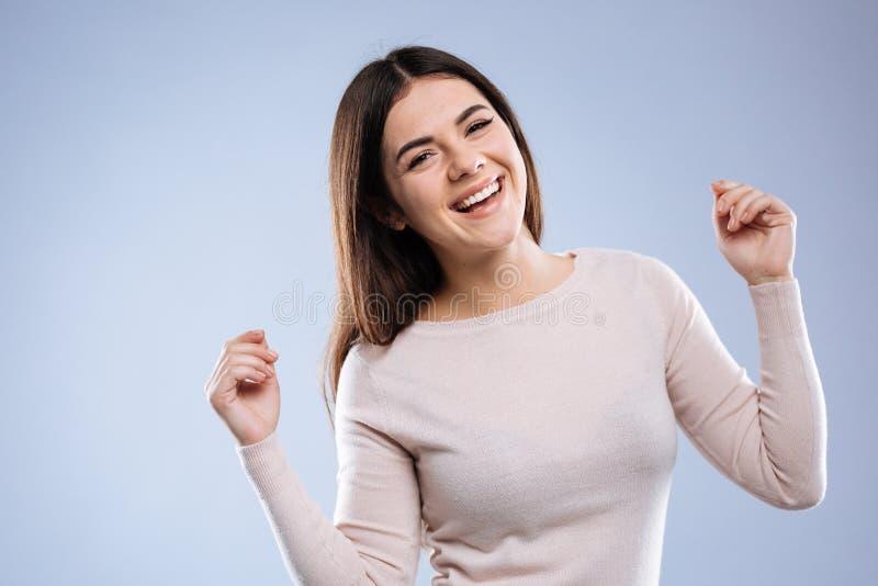 Donna allegra positiva piacevole che ritiene molto felice fotografie stock