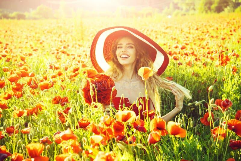 Donna allegra su un giacimento di fiore ragazza nel campo del seme di papavero in retro cappello fotografia stock