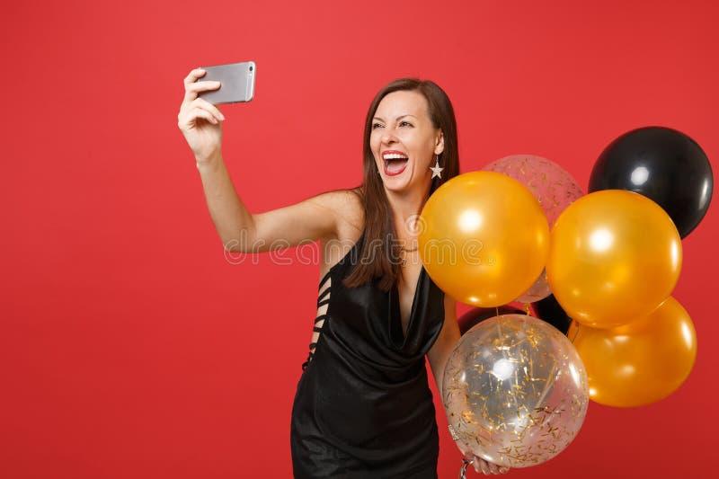 Donna allegra in vestito nero che celebra tenendo gli aerostati, facenti prendendo selfie sparato sul telefono cellulare isolato  immagini stock libere da diritti