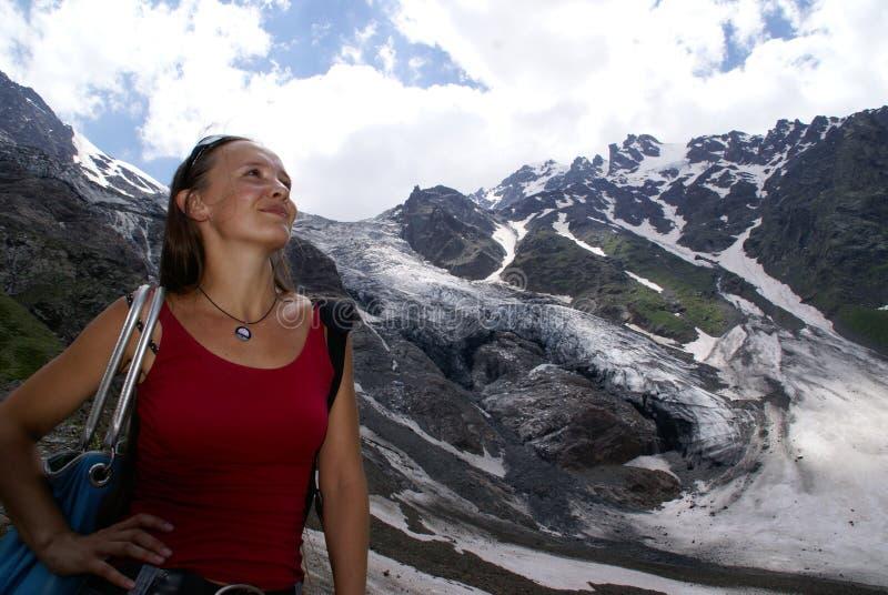 Donna alta nelle montagne, neve, vetrai, nuvole fotografia stock