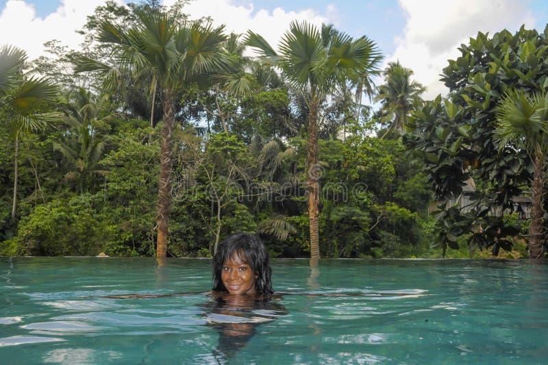 Donna americana del giovane africano nero felice attraente che gode delle feste nello stagno tropicale di infinito della località fotografia stock