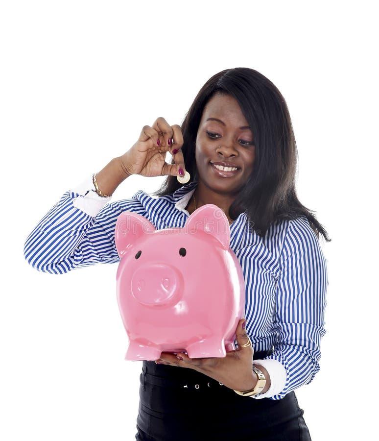 Donna americana di affari dell'africano nero che mette moneta nel porcellino salvadanaio rosa surdimensionato fotografia stock