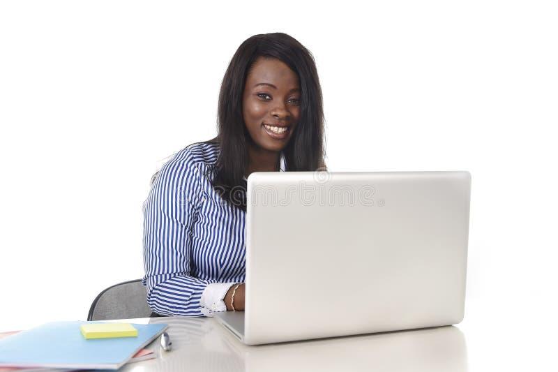 Donna americana di etnia dell'africano nero che lavora al computer portatile del computer a sorridere della scrivania felice fotografia stock libera da diritti