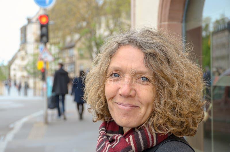 Donna amichevole sorridente che porta una sciarpa tricottata immagini stock