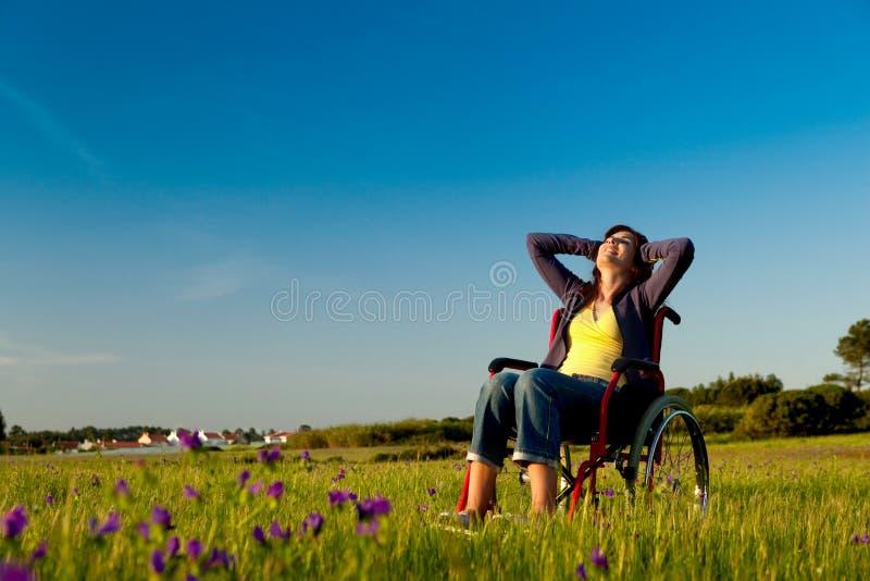 Donna andicappata sulla sedia a rotelle fotografia stock