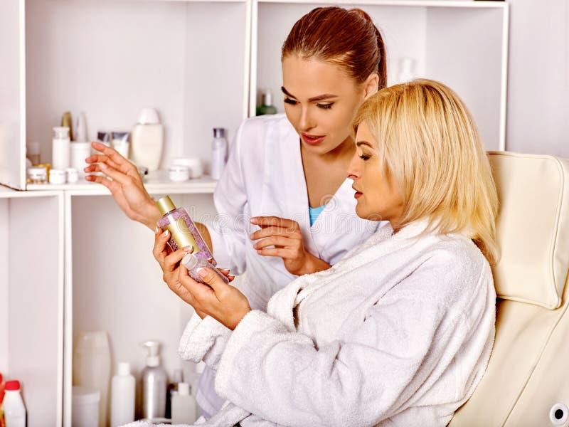 Donna 35-40 anni nel salone della stazione termale con l'estetista immagini stock