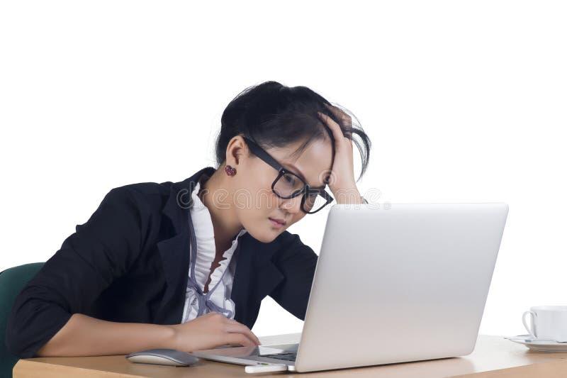 Donna annoiata di affari che lavora al computer portatile che esamina molto noioso il Th