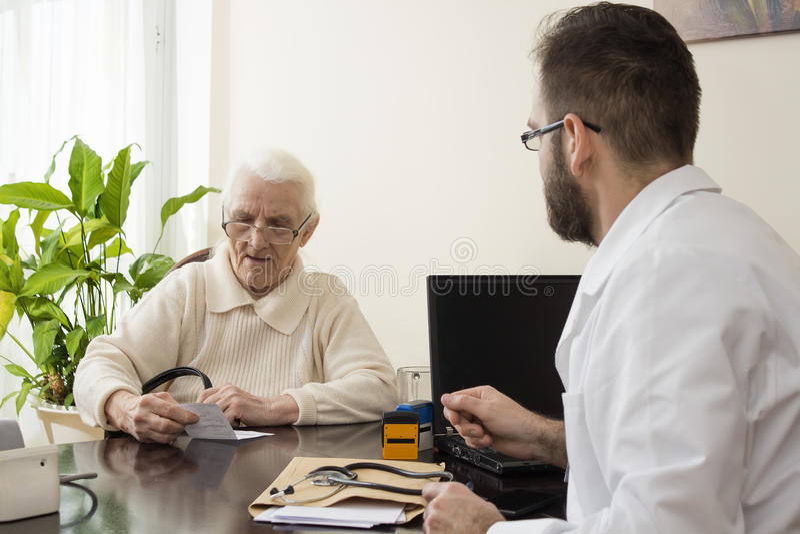 Donna anziana al geriatra di medico medico del geriatra con un paziente nel suo ufficio immagine stock libera da diritti