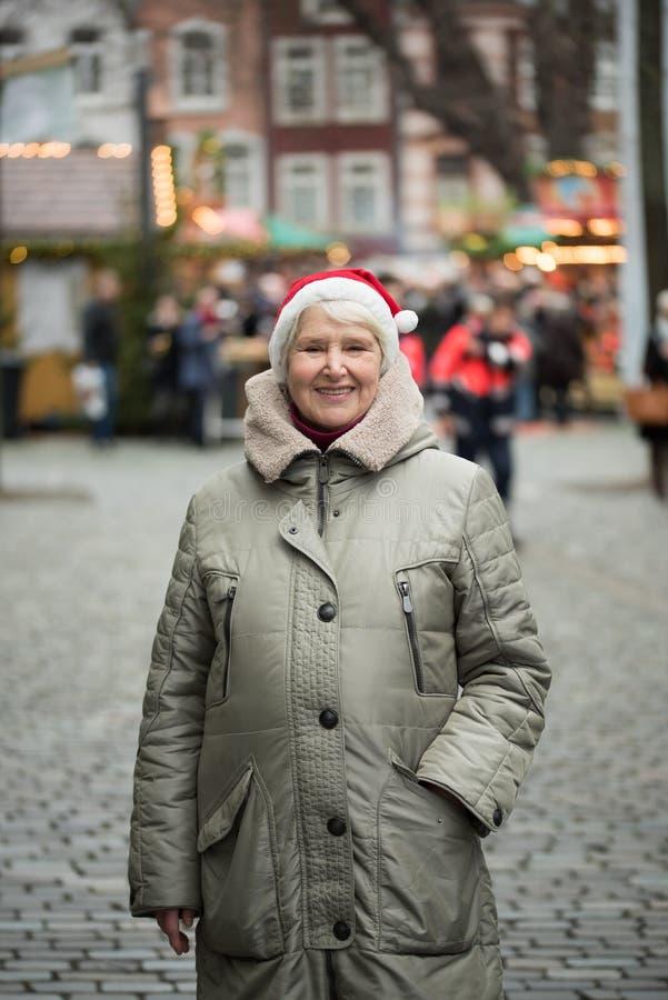 Donna anziana al mercato di Chrismas fotografia stock libera da diritti
