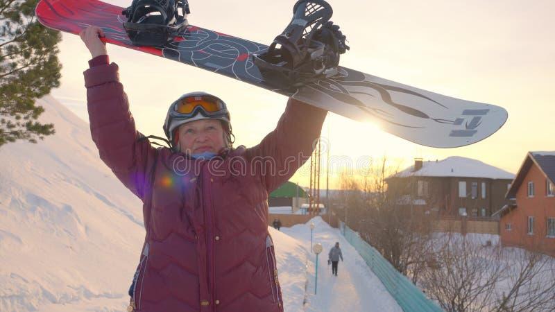 Donna anziana allegra che aumenta sulle mani con lo snowboard dopo riuscito sul pendio della neve immagine stock