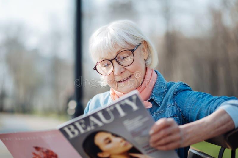 Donna anziana allegra che legge una rivista immagine stock