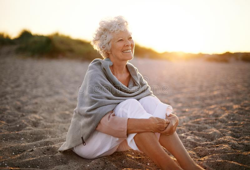 Donna anziana allegra che si siede sulla spiaggia fotografia stock