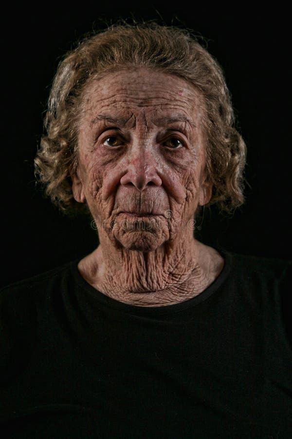 Donna anziana anziana su fondo nero immagini stock libere da diritti