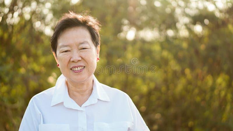 Donna anziana asiatica felice che sorride in sole di mattina con la parte posteriore di verde immagine stock