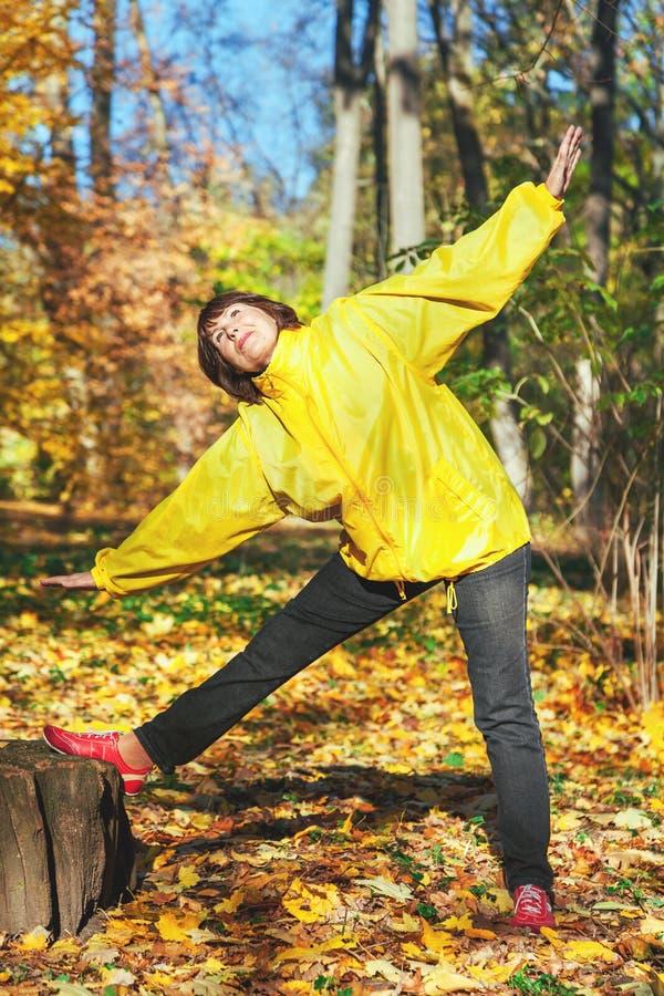 Donna anziana attiva che fa gli esercizi relativi alla ginnastica nella radura della foresta fotografie stock libere da diritti