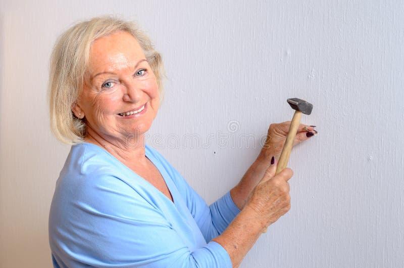 Donna anziana capace sorridente che fa DIY immagine stock libera da diritti