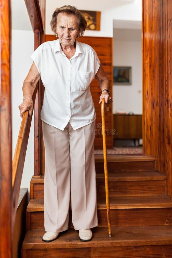 Donna anziana a casa facendo uso di una canna per scendere le scale fotografia stock